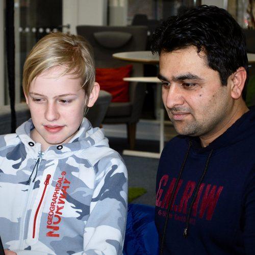 Deltagaren Adam får hjälp läraren Ihklaq med att lägga in funktioner på sin hemsida.